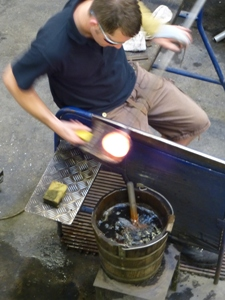 Glassblower using newspaper paddle